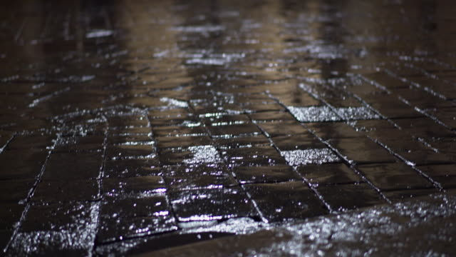 Stone pavement and arcades during the rain at night