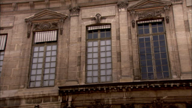 stone pediments top windows in a courtyard. available in hd. - frontgiebel stock-videos und b-roll-filmmaterial