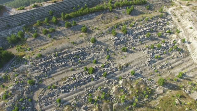 aerial: stone quarry on mountain plateau - stone material stock videos & royalty-free footage