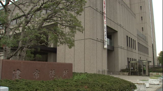 a stone sign identifies tsu city hall in japan. - local government building stock videos & royalty-free footage