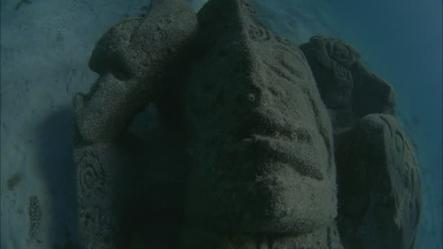 SLO MO POV Stone statue head on sandy ocean floor / Moorea, Tahiti, French Polynesia
