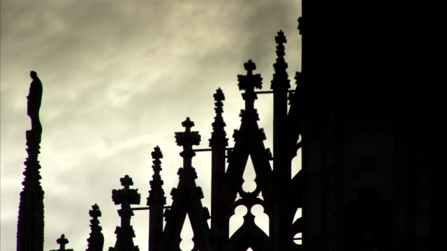 a stone statue stands on top of a spire of the milan cathedral at dusk. available in hd. - spire stock videos & royalty-free footage