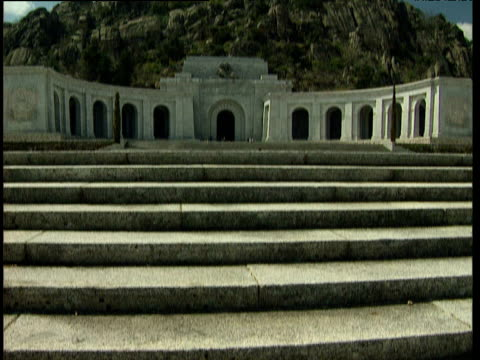 Stone steps leading to basilica tilt up to white marble archways and to huge stone cross on rocky hill Valle de Los Caidos.