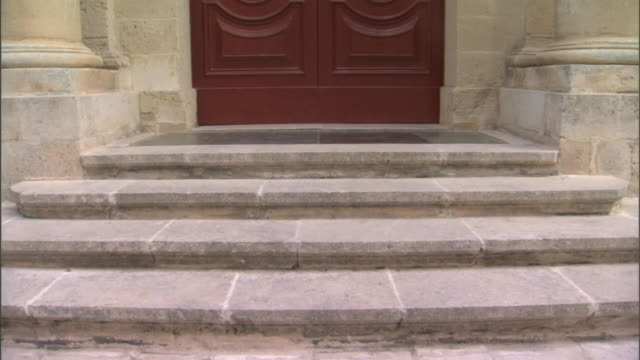 stone steps tu ws oversized limestone columns flanking residential entrance w/ red double doors handmade brass weathered patina maltese habbata... - door knocker stock videos & royalty-free footage