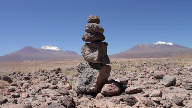 MS PAN Stone structure in desert  stony brown plain with snowy mountains