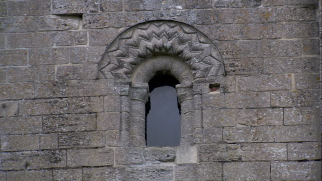A stone tower features an arched window. Available in HD.