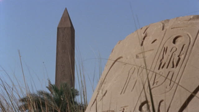 MS Stone with hieroglyphics with obelisk in background at Luxor Temple/ PAN CU Hieroglyphics/ Luxor, Egypt