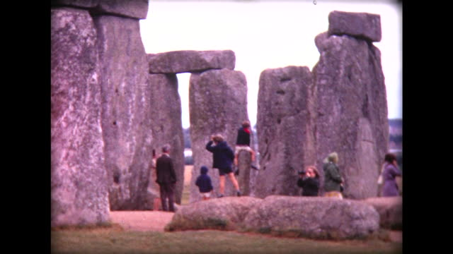 1971 stonehenge and kids crawling on stones - 1971 stock-videos und b-roll-filmmaterial