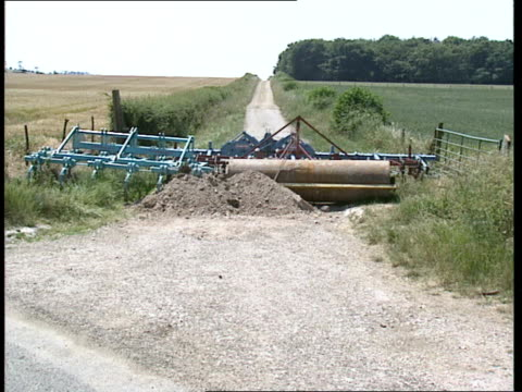 vídeos y material grabado en eventos de stock de summer solstice; farmers left heavy farm machinery across lane to stop camps being set up / convoy of police vans arriving at the stones night gv's... - solsticio de verano