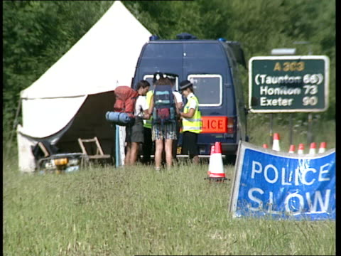 summer solstice; itn england: wiltshire: ext various shots of stonehenge / police guarding entrance / police stopping hippies as they walk along road... - wiltshire stock videos & royalty-free footage