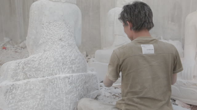 cu, pan a stonemason carves a marble buddha statue in mandalay's stone carving district / mandalay, myanmar - carving craft activity stock videos and b-roll footage