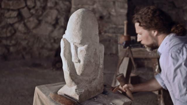 vídeos de stock e filmes b-roll de stonemason pedra esculpida com martelo e cinzel - escultura