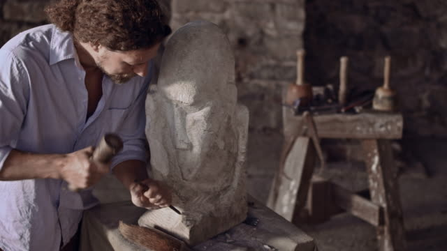 stonemason carving stone with hammer and chisel - stone object stock videos & royalty-free footage