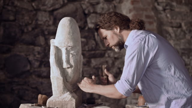 stonemason carving stone with hammer and chisel - stone material stock videos & royalty-free footage