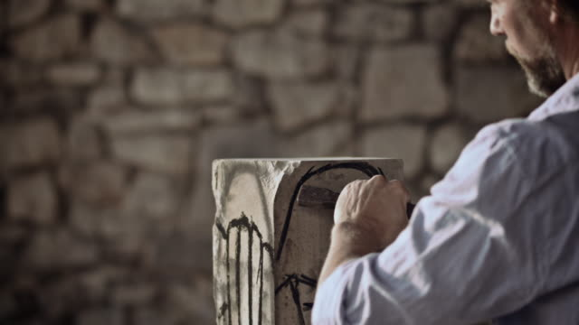 stockvideo's en b-roll-footage met stonemason carving stone with hammer and chisel - snijwerk