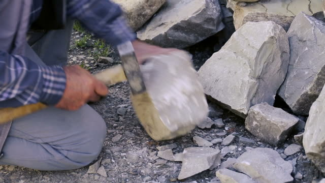 stockvideo's en b-roll-footage met stonemason cutting a block of granite with sledgehammer. - snijwerk