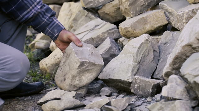 Stonemason cutting a block of granite with sledgehammer.
