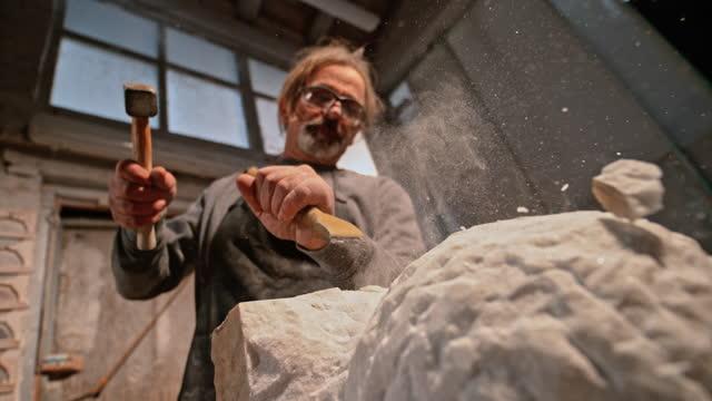 ハンマーでノミを打つslo mo ldストーンメーソンと石の破片が空中に飛ぶ - 中年の男性一人点の映像素材/bロール