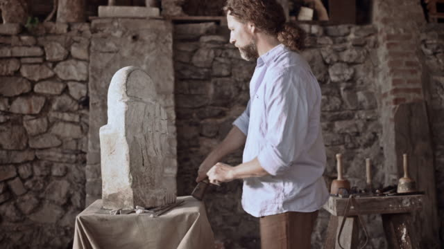 stockvideo's en b-roll-footage met stonemason starts carving stone with hammer and chisel - snijwerk