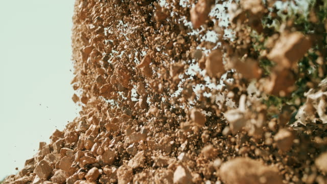 slo mo stones falling down in sunshine - roccia video stock e b–roll