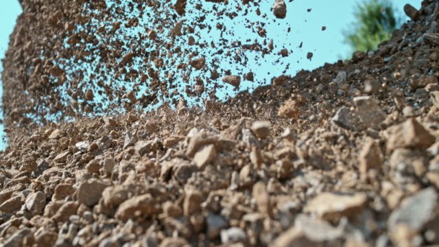 slo mo stones falling on a pile in sunshine - construction material stock videos & royalty-free footage