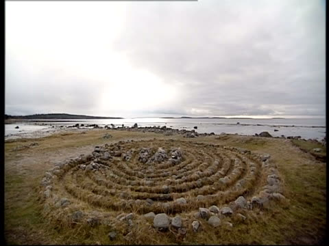 Stones form concentric circles near the sea.