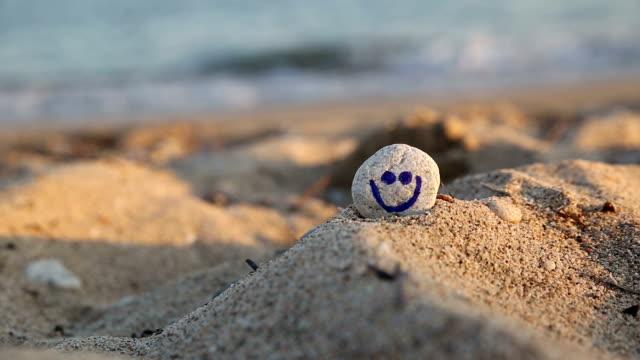 steine am strand mit einem lächeln - symbol stock-videos und b-roll-filmmaterial