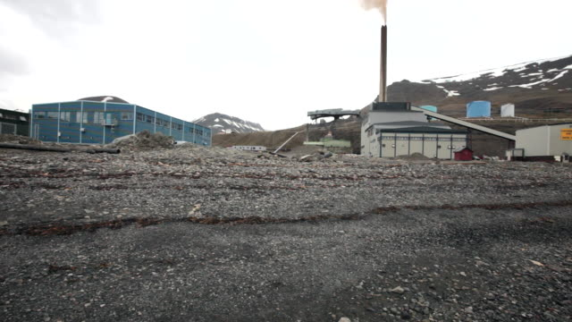 a stony beach and a power station in the back in longyearbyen, spitsbergen, svalbard - スヴァールバル諸島およびヤンマイエン島点の映像素材/bロール