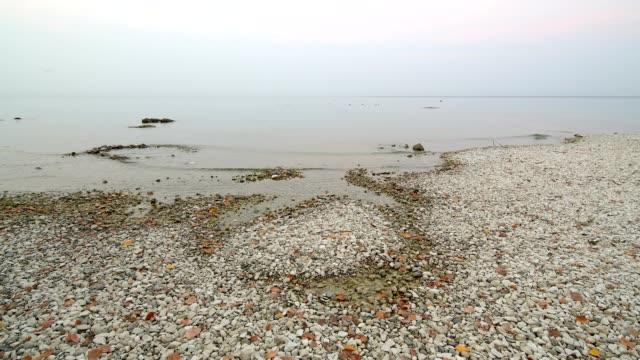 stony lake shore at dawn, lake garda at sunrise, garda, lake garda, lago di garda, veneto, italy - lago stock videos & royalty-free footage