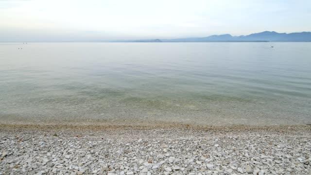 stony lake shore, garda, lake garda, lago di garda, veneto, italy - lago stock videos & royalty-free footage