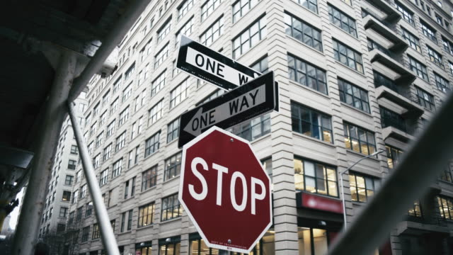 stop and one way signs against building in city - road sign stock videos & royalty-free footage