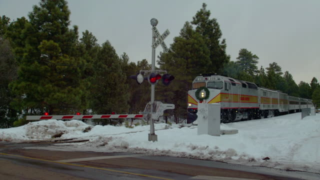 A stop bar lowers at a railroad crossing as a Grand Canyon train travels over snow-covered ground.