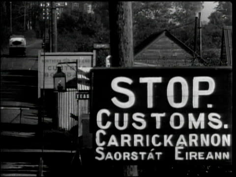 vídeos de stock e filmes b-roll de ms 'stop customs' sign on border road between northern ireland eire customs office checking women's baggage ms custom agent - 1944