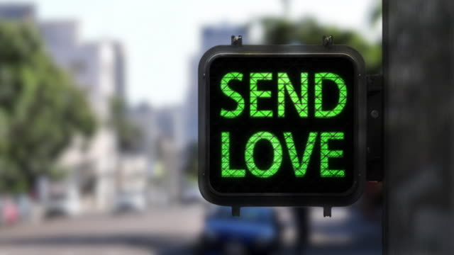 stop hate. send love—medium shot of walk signal with hopeful social message - green light stock videos & royalty-free footage