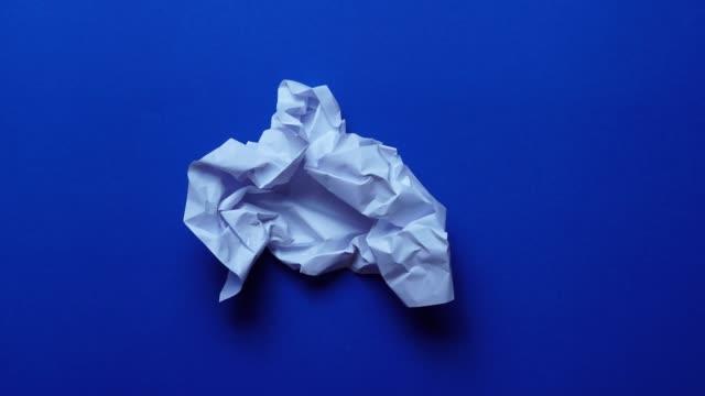 vidéos et rushes de arrêter les rides de papier d'animation de mouvement faisant une boule de papier sur le fond bleu - un seul objet