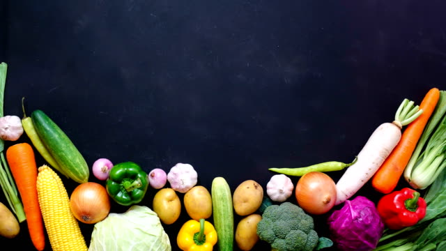 Stop motion animation top view vegetables and pan on black color background for copy space
