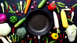 stop motion animation top view vegetables and pan on black color background