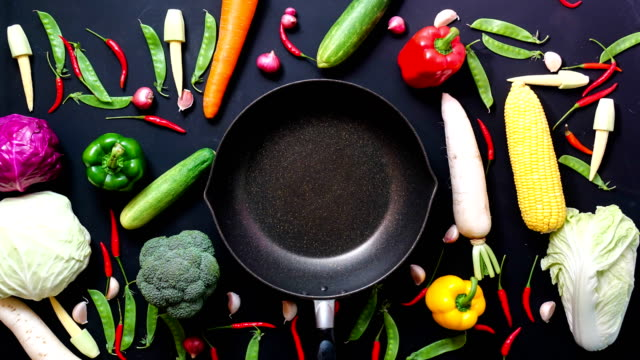 stop motion animation top view vegetables and pan on black color background - food and drink stock videos & royalty-free footage