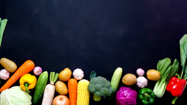 stop motion animation top view vegetables on black color background for copy space - vegetable stock videos & royalty-free footage