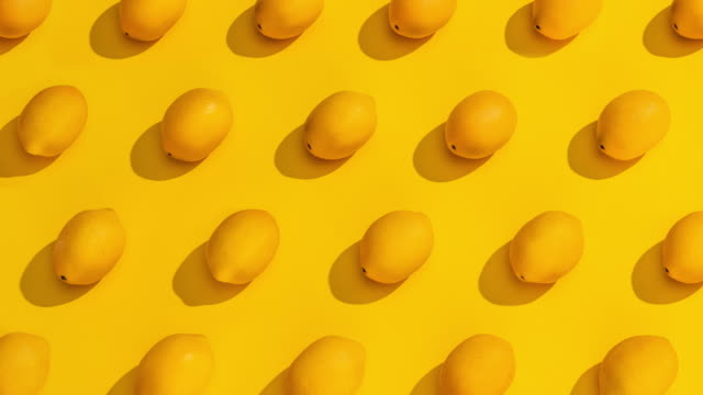 vídeos de stock e filmes b-roll de stop motion collection of lemons on a yellow background. - fruta