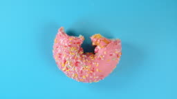 Stop motion creative concept video animation donut bite on blue background.