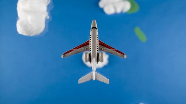 Stop Motion Model aeroplane flying through clouds/ studio shot