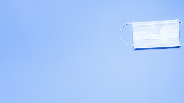 stop motion of a face pollution mask against a blue background - biomedical animation stock videos & royalty-free footage
