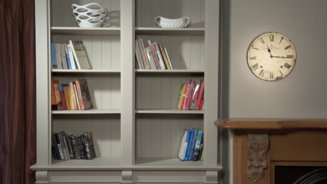 ms t/l stop motion of books arranging in bookshelf, time changing clock on wall / auckland, north island, new zealand - order stock videos & royalty-free footage