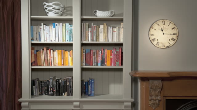 ms t/l stop motion of books disappearing from bookshelf, time changing clock on wall / auckland, north island, new zealand - arranging stock videos and b-roll footage