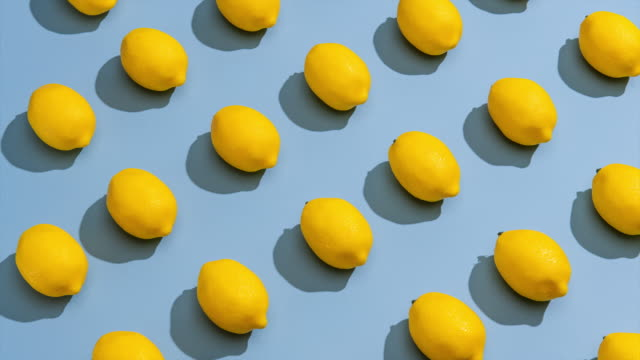 stop motion  of lemons on a blue background. - lemon stock videos & royalty-free footage