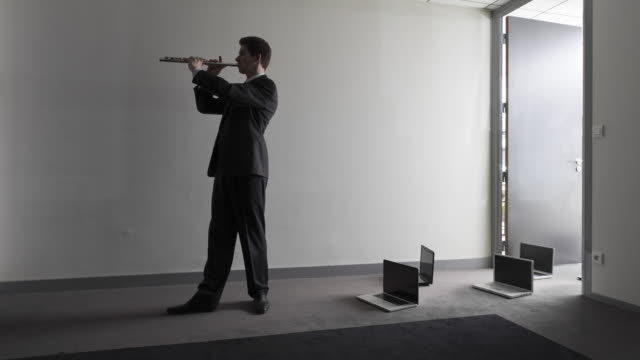 Stop Motion Pan shot of businessman conducting laptops with his flute