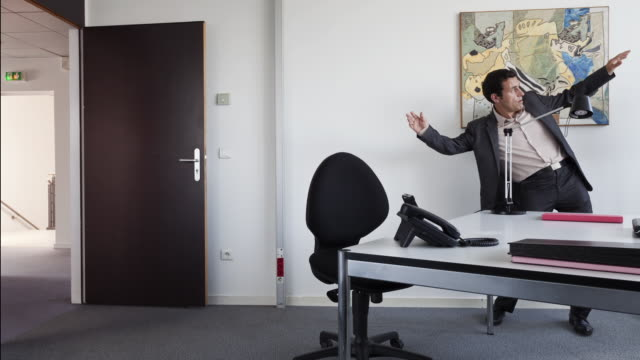 vidéos et rushes de stop motion / pixilation pan shot of businessman skating along floor with normal shoes while entering his office and sitting - chaise