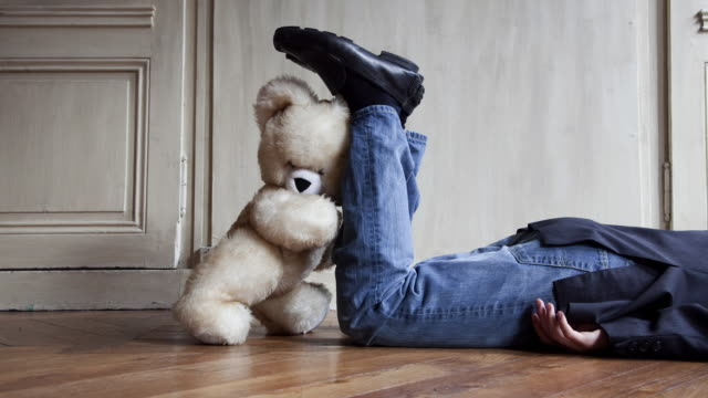 stop motion / pixilation shot of teddy bear pushing young man lying on the floor in apartment - oggetto creato dall'uomo video stock e b–roll