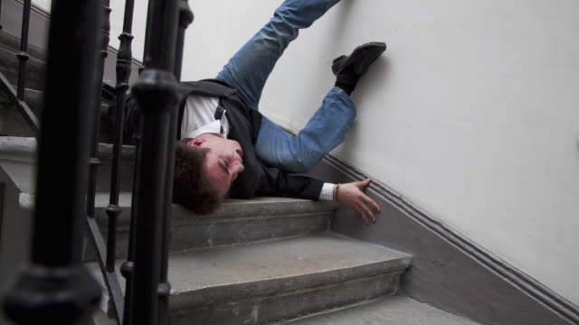 stop motion / pixilation shot of young businessman falling in stairs of an apartment building - staircase stock videos & royalty-free footage